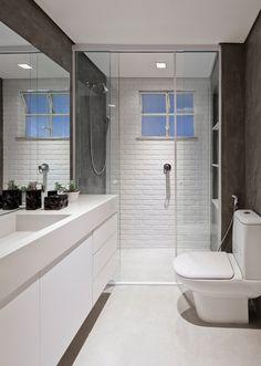 Banheiro social com revestimento cerâmico estilo tijolinho branco em uma das paredes, em todas as outras textura de cimento. Piso cinza claro e bancada branca. Decoração de Apartamento em Higienópolis, São Paulo