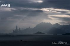 A commuter ferry (bottom R) sails towards Hong Kong island as light shines through clouds in the skies above on November 25, 2016. Anthony WALLACE / AFP