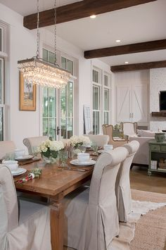 Coastal home tour - love the open dining room with parsons chairs and crystal chandelier and the rustic ceiling beams eclecticallyvintage.com