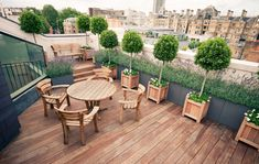 Landscapes by Jonathon Stollar. A ROOFTOP TERRACE GARDEN IN SW1. The regimented bays and geraniums offer a uniformed contrast to the London sprawl below in this SW1 roof terrace, entertainment space and garden.  We also sourced Gaze Burvil oak furniture as it complimented the welsh slate facade, Iroko planters from Oxford Planters and large faux lead troughs, cast for us by Capital Garden Pots. At night the bay trees are uplift with John Cullen lights.