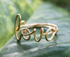 http://www.etsy.com/listing/85222151/gold-wire-love-ring-adjustable-band?ref=cat_gallery_13