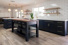 Custom floating reclaimed shelves flank the farmhouse apron sink and play off the walnut kitchen island top while creating a textural contrast against the polished tile wall. Where the three vintage-style pendants now hang, there was a large wall closing off the entire kitchen. Demolishing the wall gave an opportunity to marry the two spaces and allow for bar seating.