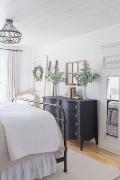 Taking you on a tour of our farmhouse bedroom all decorated for Spring. Rich textures and fresh flowers help to create a light + airy space that still feels cozy and warm. #farmhouse #farmhousestyle #bedroom #spring #springdecor