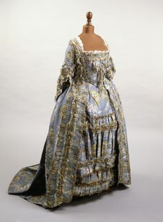 Blue silk and linen taffeta brocade sack-back dress (front view), 1764-66. An ensemble consisting of dress, stomacher, and petticoat. The skirt or petticoat is trimmed with lace and matching fly braid.