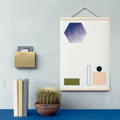 You can hang your favorite poster on the wall in a new way using the wooden frames by Ferm Living. The frames don't have any background or side parts and the wooden supports are put in the top and bottom parts of the poster.