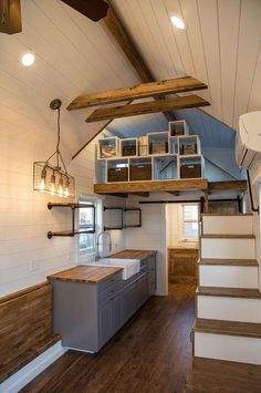The modern galley kitchen includes gray cabinets, butcher block counters, open pipe shelving, and a farmhouse sink.