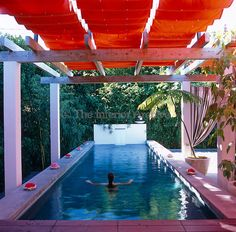 Designer Antonia Hutt relaxes in her outdoor swimming pool covered with a retractable orange awning