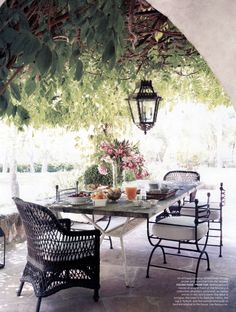 An antique hanging lantern and vintage wicker and iron chairs on this peaceful terrace...