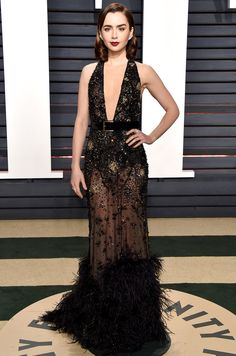 LILY COLLINS wears a sheer, plunging and spangled Elie Saab with a feather hem to the Vanity Fair after party.