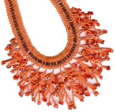 Coral Cat's Eye Chip Twig Cascade, a bead-netted necklace designed around coral-colored cat's eye (fibre-optic) glass chips. Shows how careful choice of colours can tame strong base colours and make a monochrome palette work. Pattern by Maria Rypan, beaded by Jo-Ann Woolverton.