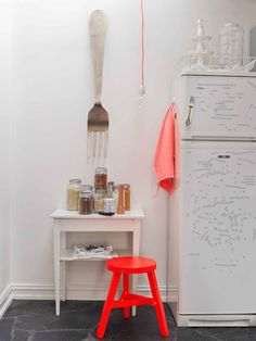 We love the drastic look of this neon orange stool in the white kitchen!