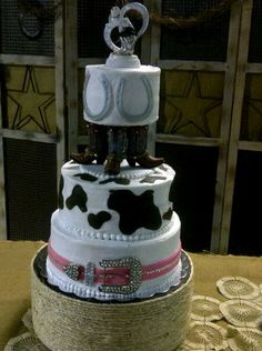 This is a western wedding cake I made. Buttercream with fondant cowprint, horseshoe and belt accents.  Stand was a round shaped box covered with rope using a hot-glue gun.  Cake topper and boots came from Hobby Lobby. By Robyn Montgomery, Grandview, Texas.  See my facebook link for further info. https://www.facebook.com/robyn.montgomery.35
