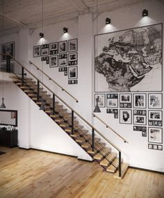 Gorgeous gallery wall created with a collection of black and white images and an oversized map. The arrangement of the images works with the shape of the stairs as they ascend to the loft. {via home designing}