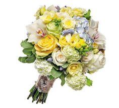 Bouquet of blue hydrangeas; cymbidium orchids; snowball viburnum; cream, yellow, and green roses; freesia; yellow coxcomb, and blue muscari,
