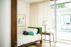 Mid century modern bedroom neutral with pops of green.  Plum Modern linens