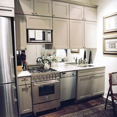 Gray cabinets with antique brass handles..mirror instead of backsplash helps brighten the small space