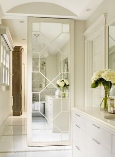 A sliding mirrored door separates the vanity area from other parts of the master suite. Interior design: Courtney Giles Decker. Photography: Emily Followill. See more of this bathroom at www.StyleBlueprint.com.