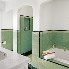 1930s vintage bathroom: black outlined tile work in spring green that extends up the wall and outlines built-in niches
