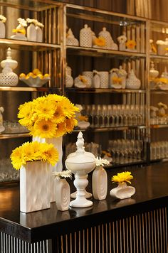 Placing vases of varying heights at the corner of a bar creates texture and depth within the space.