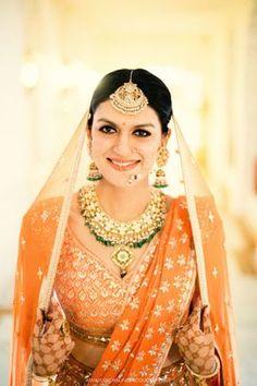 Stunning bride in tangerine lehenga with kundan and beads necklace | Jai & Misha wedding story | WedMeGood #wedmegood #indianbride #lehenga #lehengacholi #bridaljewellery #jewellery #kundan #orangelehenga