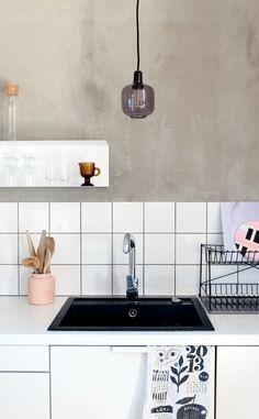 Kitchen concrete wall, tile backsplash and black sink. All by KOTIPALAPELI