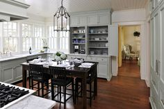 LOVE about this kitchen: windows all around, cabinets that look like furniture, tall kitchen table, breakfast bar cabinets.