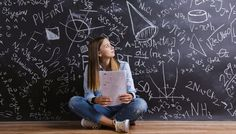 A girl looks at mathematics concepts on a blackboard