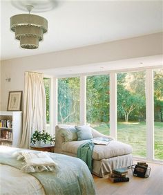 chaise by large window panes with a favorite throw and books