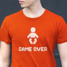 """Father's Day is coming up, and we have the perfect gift for the new dad. This """"GAME OVER"""" T-Shirt for New Dad is his way of announcing to the world that his party days are over. Late nights out drinking with his bros have taken a back seat to his new favorite person. Game Over. The shirts are comfortable and safe to wash, in case the baby spits up on it. Buy one in orange, cranberry, navy, black, teal or kelly green. Use coupon code PINFIVE for 5% off!"""