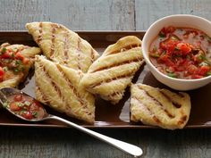 Brush prepared pizza dough with olive oil and garlic, sprinkle with cheese, then grill until char marks appear for easy Garlicky Grilled Flatbread Strips with Fresh Tomato Sauce.
