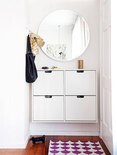 "Lauren created an ""entry"" with wall-mounted shoe storage, mirror, hooks and rug."