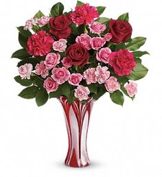 "The art of romance! A gift in and of itself, this amazing art-glass vase is an exceptional showpiece for a dramatic bouquet of red and pink roses.  Red roses, pink spray roses and hot pink carnations are accented with fresh lemon leaf. Delivered in a Swirls Of Love vase.  Approximately 17"" W x 21"" H  Orientation: One-Sided    Click on image to order"
