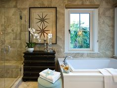 Travertine-style porcelain tile and clean white surfaces define this spa-like master bath, where an antique-style dresser and botanical artwork offer an intriguing focal point.  http://www.hgtv.com/dream-home/hgtv-dream-home-2013-master-suite-bathroom-pictures/pictures/page-12.html?soc=dhpp