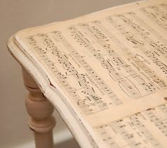mod podge sheet music onto coffee table then seal. this will be a weekend project for me very soon.