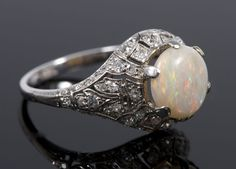 Art Deco opal and diamond cocktail ring with circular polished opal measuring approximately 9mm diameter in a domed pierced setting.