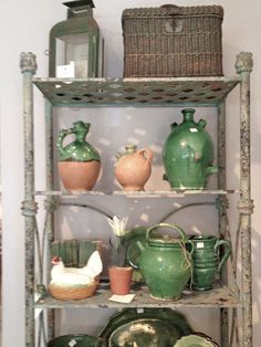 """The green lantern, pottery, and antique books look wonderful on this aged iron shelving unit.""  Brooke Giannetti.  Shelving unit, etc., Marston Luce Antiques."