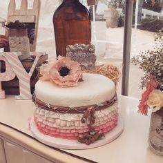 Vintage cowgirl cake. Lots of soft pink ruffles with vines of flowers. the birthday girl's name on the belt buckle and of course gumpaste poppies. Beautiful display showcasing the cake by event stylist Elly O.