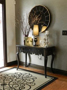 Nice Entry Way/ Love the rug ( a plain jute rug with a black border and then painted with a design?) and the mirror. Two tones on walls, interesting.