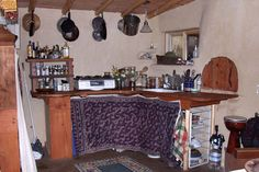 Small cob house kitchen.   Looks to be a wrap used as the cabinet curtain.   Nice idea!