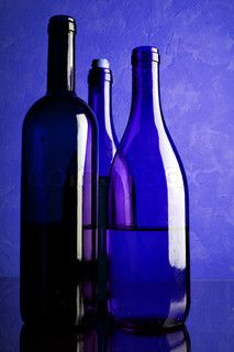 Still-life with three wine bottles toned in blue color