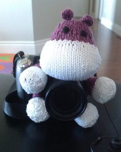 Free Knitting Pattern for Say Cheese Camera Puppet - Get a smile for the camera from babies and children with this adorable hippo that slips over the lens of your camera. You can also use other head and feet patterns and adjust the size for your camera lens. Designed bySumiko Sumiko