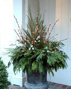 Add pre-lit branches to a container packed full of cedar and pine sprigs for a gorgeous holiday display.