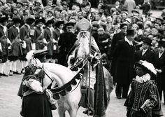 Sinterklaas op zijn paard. Twee Pieten staan ernaast. Op de achtergrond mannen in historische kleding. Amsterdam, 15 november 1959.