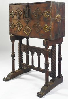 A SPANISH POLYCHROME AND PARCEL-GILT WALNUT VARGUEÑO  17TH CENTURY  the rectangular case enclosing thirteen drawers, on a later walnut stand.  height of case 25 in.; overall height 5 ft. 1/2 in.; width 41 3/4 in.; depth 28 in.  63.5 cm; 153.5 cm; 106 cm; 71cm
