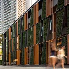 A checkered living garden facade in Bangkok features a combination of glass, plants and shutters.
