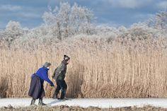 Deze foto heb ik gemaakt in januari 2009 tijdens een toertocht op de schaats bij Dwarsgracht (gem. Giethoorn). Het contrast tussen de vrouw in klederdracht en de man samen met het winterse landschap vind ik typerend voor Nederland. #Overijssel #Staphorst