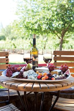 Fresh fruit and artisanal cheeses give this outdoor table setting a rustic charm. #Wine #Cheeses #Tablesetting