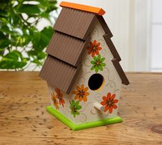 Bright daisies decorate this sweetly shingled birdhouse. Make this craft using FolkArt paints. The wooden birdhouse can be found at your local Walmart. #woodenbirdhouses