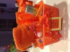 Orange you glad it's summer! Gift for teacher beach towel, orange ice tray, orange cup, orange drink, orange trident gum, orange mints, orange hand sanitizer, orange clean and clear face wash, and a orange colored tube of sunscreen.