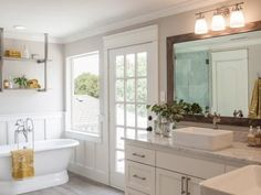The newly remodeled master bath has marble countertops and backsplash, a pedestal tub and walk-in shower. The space is also brightened up with a new window, expanded door and updated white trim.